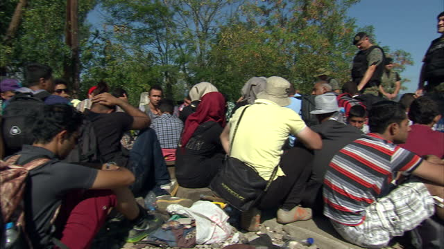 exterior shots of refugees waiting to be transported to serbia on the border of macedonia and greece, and police wearing riot gear, chasing refugees... - 2015 stock-videos und b-roll-filmmaterial