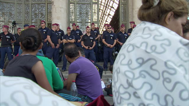 exterior shots of refugees waiting waiting outside keleti station, with police officers stood on the side on september 3, 2015 in keleti, hungary. - budapest stock-videos und b-roll-filmmaterial