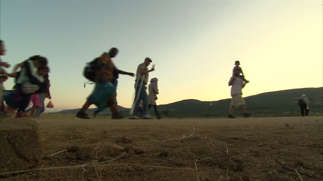 exterior shots of refugees walking along a road with their belongings on august 24, 2015 in presevo, serbia. - 2015 stock-videos und b-roll-filmmaterial