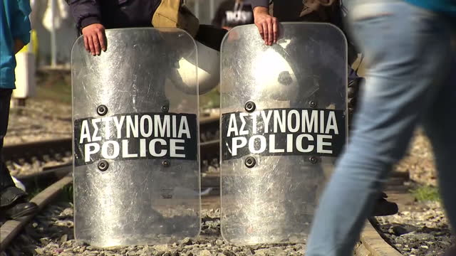 exterior shots of refugees walking around train tracks at greece-macedonia border; shots of police officers guarding train tracks; shots of parents &... - guarding stock videos & royalty-free footage