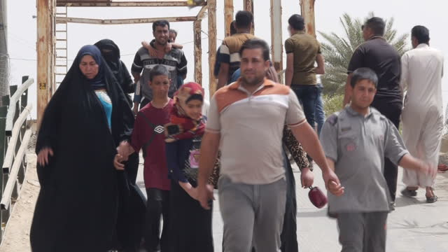 Exterior shots of refugees walking over bridge carrying belongings supplies in wheeled carts and cattle on April 21 2015 in Anbar Iraq