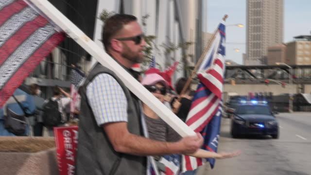 exterior shots of republican protestors waving flags and banners outside state farm arena on 5th november 2020 atlanta, georgia, united states. - アメリカ共和党点の映像素材/bロール