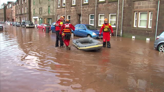 Exterior shots of rescue workers in waterproofs including life jackets red overalls yellow hard hats and waders wading through muddy floodwaters and...
