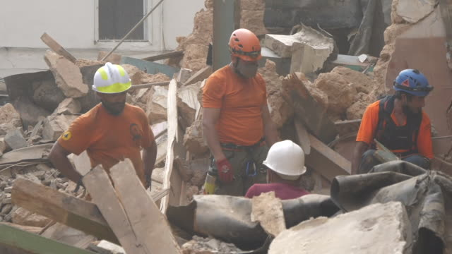 exterior shots of rescue workers searching through rubble in street of damaged and destroyed buildings one month on from the devastating port... - rescue stock videos & royalty-free footage
