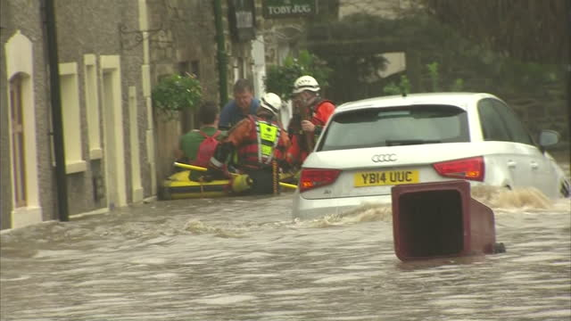 Exterior shots of rescue workers using an inflatable boat to rescue a group of people from a flooded building in Whalley>> on December 26 2015 in...