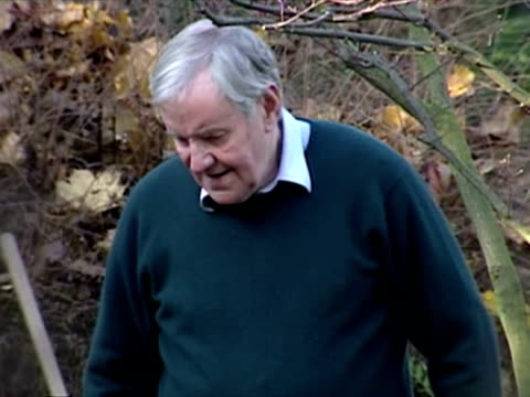 exterior shots of richard briers in garden raking leaves and cleaning pond water. richard briers doing the gardening on december 08, 2001 in england - richard briers stock videos & royalty-free footage