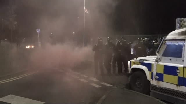 exterior shots of riot police standing behind vehicles and people throwing objects at police as another night of violent protests occur in belfast on... - danger stock videos & royalty-free footage