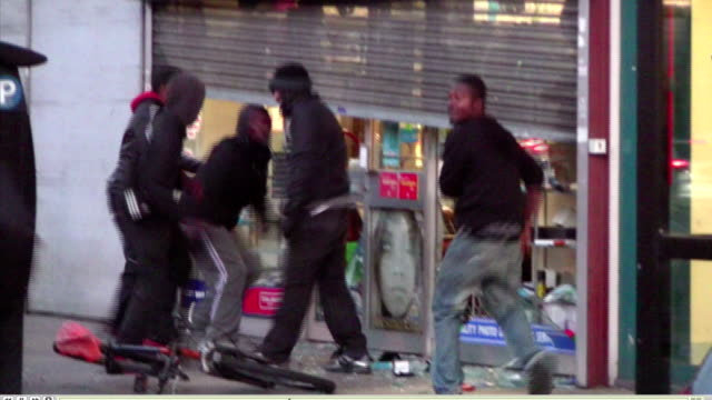 Exterior shots of rioters kicking in the windows of a partially shuttered shop during the 2011 London riots on 8 August 2011 in London United Kingdom