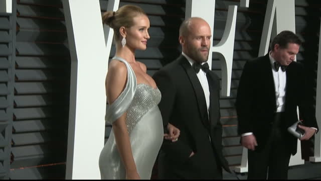 Exterior shots of Rosie HuntingtonWhiteley and Jason Statham posing on the red carpet at the Vanity Fair Oscar Party on February 27 2017 in Los...