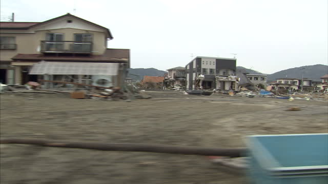 Exterior shots of rubble from completely destroyed buildings and cars after an earthquake tsunami hit the area Filmed from a car driving through the...