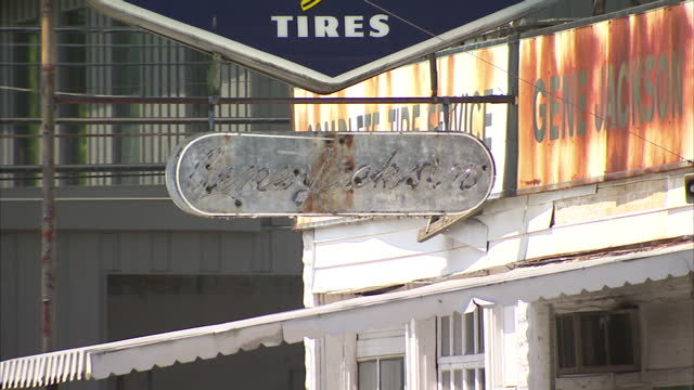 vídeos de stock, filmes e b-roll de exterior shots of rundown and derelict looking buildings in ashland kentucky including a tyre shop with rusty signs and a building with broken and... - tyre