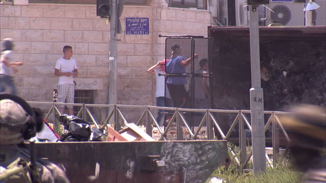exterior shots of running battles in an east jerusalem street as groups of palestinian men throw rocks towards a line of israeli army idf soldiers... - east jerusalem stock videos and b-roll footage