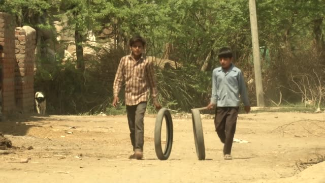 Exterior shots of rural village life with a young woman stood in a doorway of a rustic home and two young boys playing in the street with tyres and...