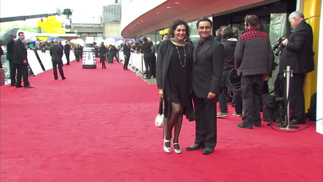 vídeos de stock e filmes b-roll de exterior shots of sanjeev bhaskar meera syal posing for photos on red carpet at bafta awards sanjeev bhaskar meera syal at bafta awards at the royal... - meera syal