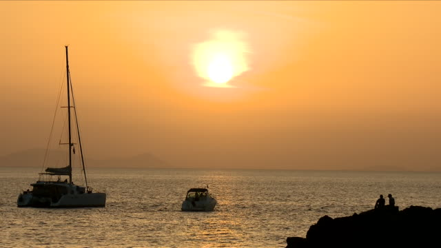 Exterior shots of Santorini harbour with a beautiful sunset as yachts and sailing boats move past on 5 June 2018 in Santorini Greece