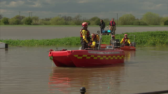 exterior shots of sara rescuers gloucestershire fire rescue service on inflatable boats wading through flood water with sticks rescue teams working... - gloucestershire stock videos and b-roll footage
