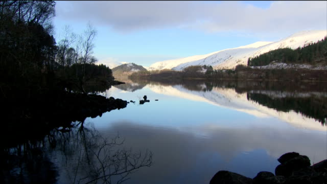 Exterior shots of scenery around Thirlmere in the Lake District with views of the snowtopped Helvellyn mountain ridge overlooking the reservoir and...