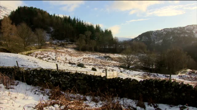 Exterior shots of scenery near Thirlmere in the Lake District with snow covering fields and hillsides and a group of walkers seen hiking across a...