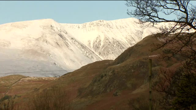 Exterior shots of scenery near Thirlmere in the Lake District with snowtopped hills overlooking a valley and a farmer feeding his sheep >> on January...