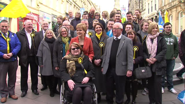 vídeos de stock, filmes e b-roll de exterior shots of scottish national party leader nicola sturgeon posing for photographs with a group of snp campaigners and supporters on april 26,... - stirling