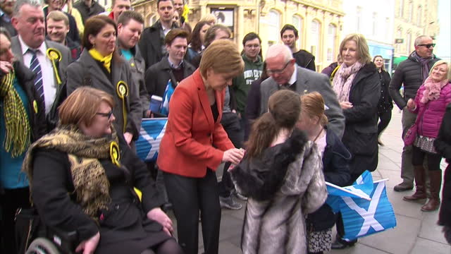 vídeos de stock, filmes e b-roll de exterior shots of scottish national party leader nicola sturgeon posing for photographs and speaking with a group of snp campaigners and supporters... - stirling