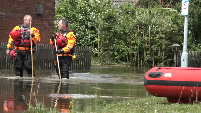 exterior shots of search and rescue workers wading through knee high flood water resident evacuating with domestic pet and a man walking his dog... - lincolnshire stock videos & royalty-free footage