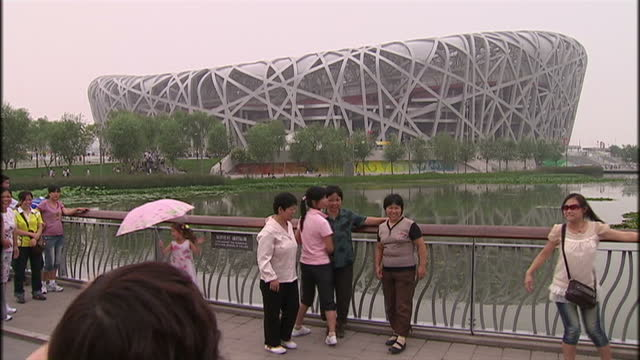 exterior shots of security guards and tourists at the bird's nest national stadium on july 30, 2009 in beijing, china. - 2008年北京夏季オリンピック点の映像素材/bロール