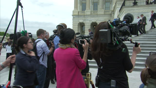 exterior shots of senators departing the capitol building with police and secret service agents stood by as anti trump protesters hold banners and... - senator stock videos & royalty-free footage