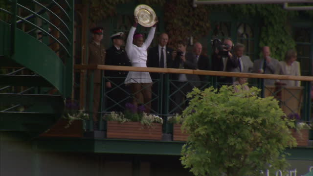 exterior shots of serena williams holding up women's wimbledon winner's trophy & waving to crowds from balcony. serena williams shows trophy to... - final round stock videos & royalty-free footage