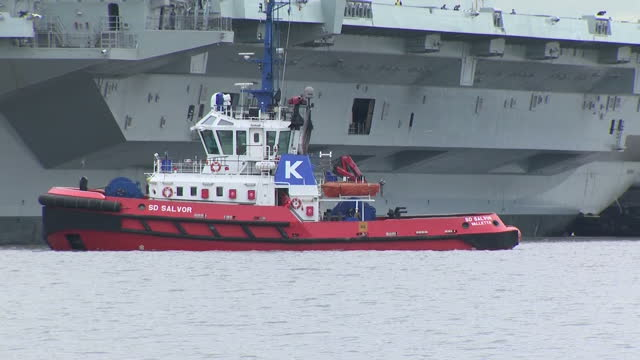 exterior shots of several tugboats assisting the hms queen elizabeth aircraft carrier as it manoeuvres out of dock on june 26 2017 in rosyth scotland - bogserbåt bildbanksvideor och videomaterial från bakom kulisserna