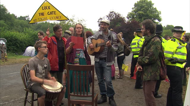 exterior shots of shale gas protesters gathered with some using hula hoops and others singing bob marley's redemption song. anti shale gas drilling... - ボブ・マーリー点の映像素材/bロール