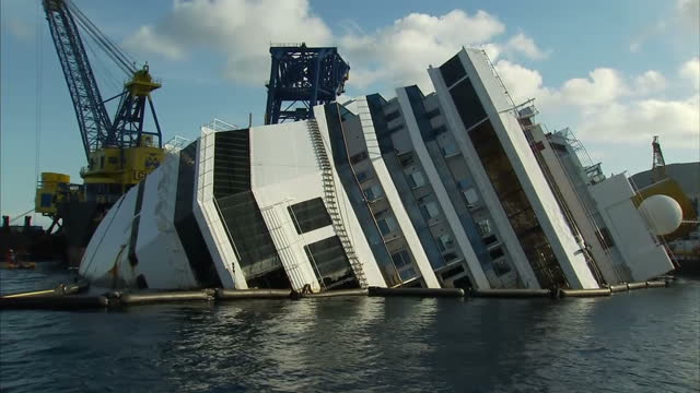 exterior shots of ship on its side from different angles surrounded by salvage boats exterior shot of costa concordia signage on side of ship costa... - giglio video stock e b–roll