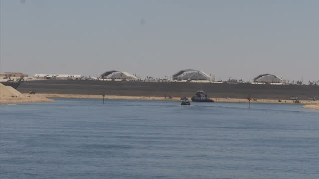 vidéos et rushes de exterior shots of ships and general port activity in suez canal and construction work underway finishing off the new canal channel on august 05, 2015... - port saïd
