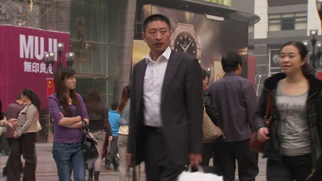 vídeos de stock, filmes e b-roll de exterior shots of shoppers on a rainy day in a pedestrianised shopping area of chongqing including designer shops such as giorgio armani and louis... - giorgio armani marca de moda