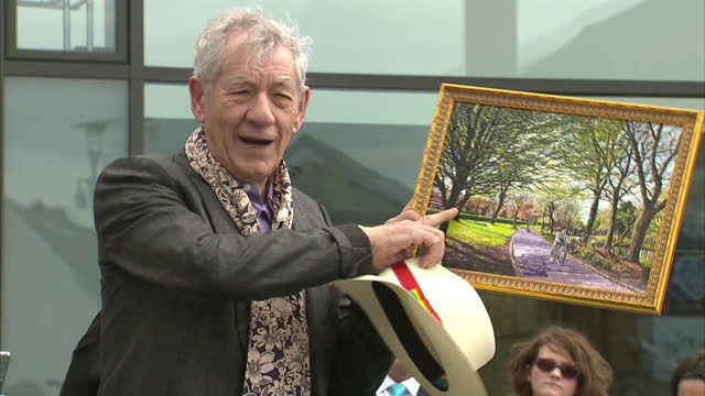 exterior shots of sir ian mckellen being presented with a pavement star outside wigan council offices - he bends down to kiss it before being... - ian mckellen stock videos & royalty-free footage