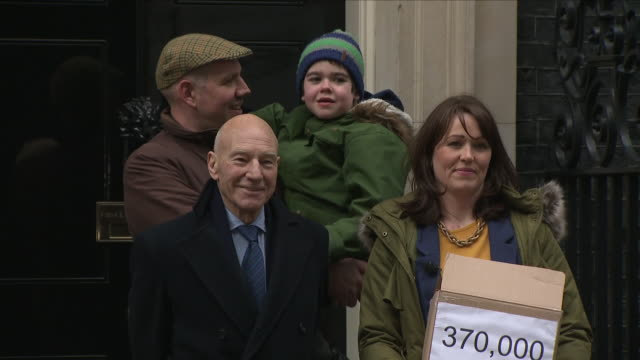 exterior shots of sir patrick stewart posing outside number 10 downing street with 6 year old alfie dingley and his parents as they present 370... - petition stock videos & royalty-free footage