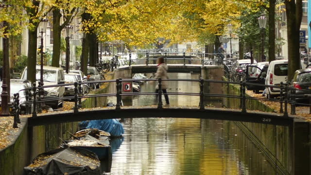 Exterior shots of small foot bridges over the a canal and a woman locking her bike up on a bridge on November 4 2016 in Amsterdam the Netherlands
