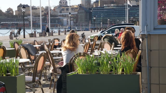 exterior shots of small groups of people sat outside a cafe on 3 april 2020 in stockholm, sweden - svezia video stock e b–roll