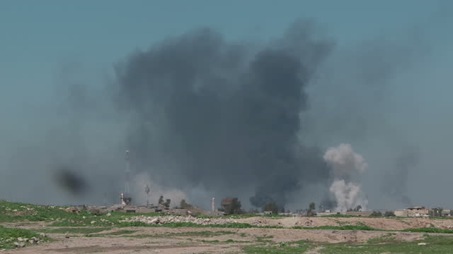 exterior shots of smoke billowing in skyline and sounds of gunfire and explosions on march 27, 2017 in mosul, iraq. islamic state is on the verge of... - イラク点の映像素材/bロール