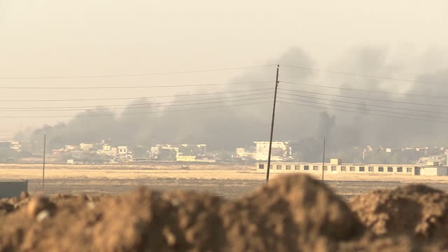 stockvideo's en b-roll-footage met exterior shots of smoke from airstrikes rising over a town outside mosul as iraqi and peshmerga forces continue their assault on isis positions on... - isis