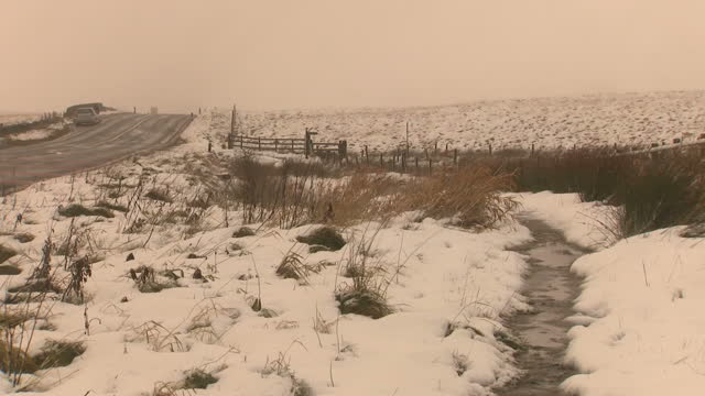Exterior shots of snow covering Saddleworth Moor and cars driving along a rural road in overcast Wintery weather on November 26 2017 in Oldham England