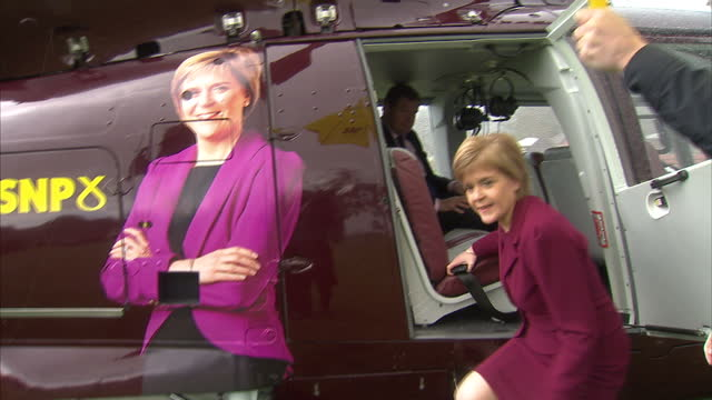 exterior shots of snp leader nicola sturgeon arriving in dundee by helicopter, and being escorted to a campaign car with an snp umbrella on may 1,... - スコットランド ダンディー点の映像素材/bロール