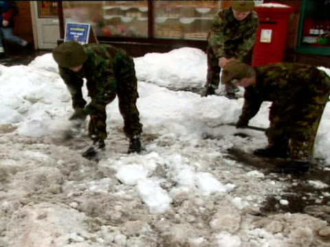 exterior shots of soldiers clearing snow in front of post office and interview with major adrian williams - 水の形態点の映像素材/bロール