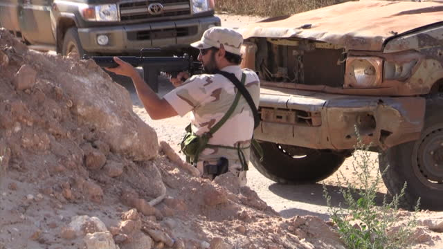 stockvideo's en b-roll-footage met exterior shots of soldiers fighting for national army of libya fighting islamic state extremists throughout the city using large weapons and firearms... - libië