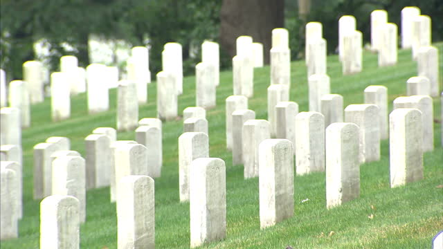 vídeos de stock e filmes b-roll de exterior shots of soldier's graves in arlington national cemetery and two anonymous women sat on the grass on january 16 2016 in washington dc - cemitério nacional de arlington