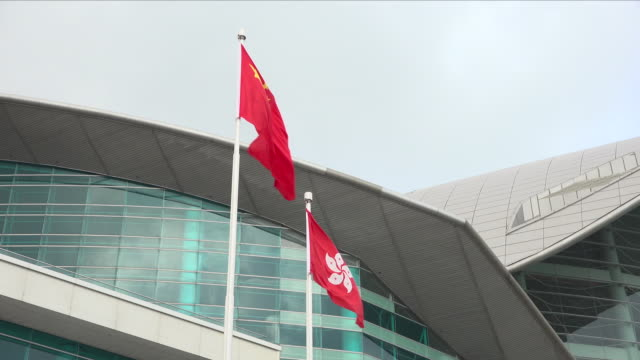 exterior shots of soldiers taking part in a flag raising ceremony in at the hong kong convention and exhibition centre raising chinese and hong kong... - ausstellung stock-videos und b-roll-filmmaterial