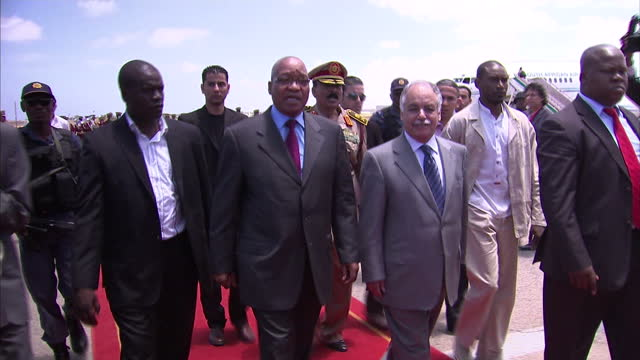 vidéos et rushes de exterior shots of south african president, jacob zuma, and entourage walk across tarmac trying to get past press and photographers before he meets... - 50 secondes et plus