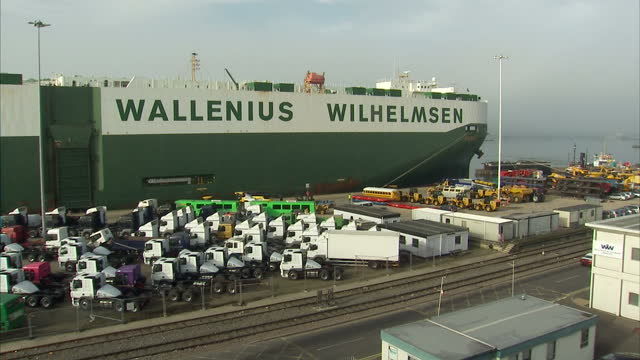 Exterior shots of Southampton Docks wth large numbers of luxury cars and lorries waiting to be loaded on board a Wallenius Wilhelmsen cargo ship on...