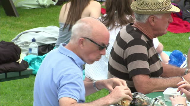 exterior shots of spectators sat on henman hill on the opening day of the wimbledon championships exterior shots of people eating lunch and watching... - campionato sportivo video stock e b–roll