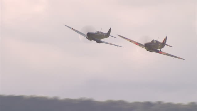 exterior shots of spitfire and hurricane planes taking part in a spectacular flypast at goodwood during the 75th anniversary commemoration event of... - airshow stock videos & royalty-free footage